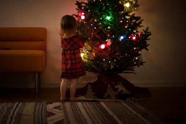 Niña decorando Árbol de Navidad