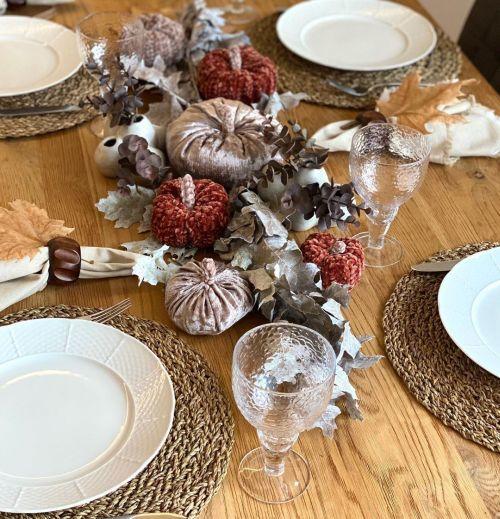 Calabazas y hojas en plata decorando mesa