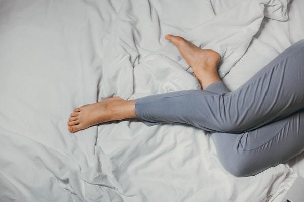 Piernas de mujer en cama de sábanas blancas