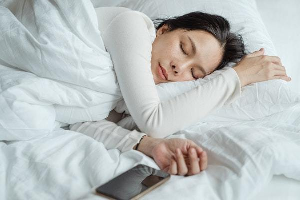 Mujer acostada en cama de sábanas blancas